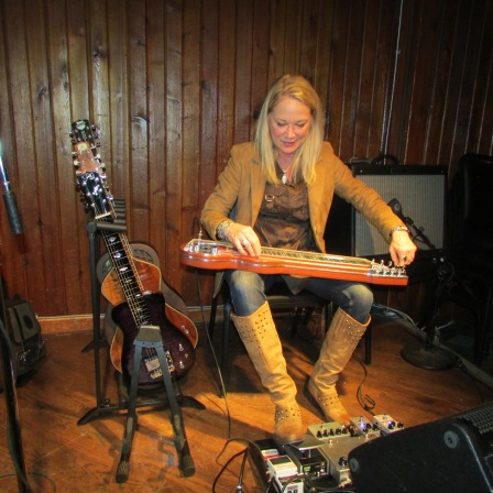 Cindy Cashdollar tuning up for Johnny Nicholas and Hellbent at the Saxon Pub.